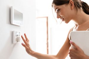 young woman entering code on keypad of home security system